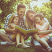 Happy family with two children   in meadow reading book together.