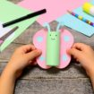 Small child holding paper butterfly in his hands. Child shows paper crafts. Funny butterfly made of colored paper. Office supplies on a wooden table. Children creativity concept