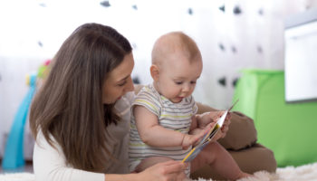 Mother showing images in a book to her cute baby son at home
