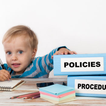 Policies and Procedure – young boy with stack of two office bind
