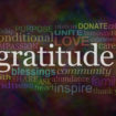 Gratitude Attitude Website Campaign Banner –  Male hands  cradling female cupped hands on a wide warm dark multicolored background with a GRATITUDE word cloud