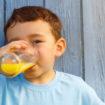 Kind kleiner Junge trinkt Orangensaft Saft trinken Textfreiraum Copyspace draußen