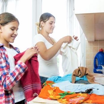 Portrait of smiling young mother with teenage daughter folding clothes after laundry