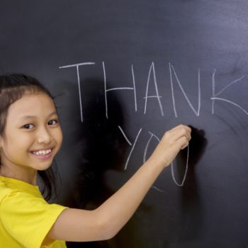 Female student writing Thank You text