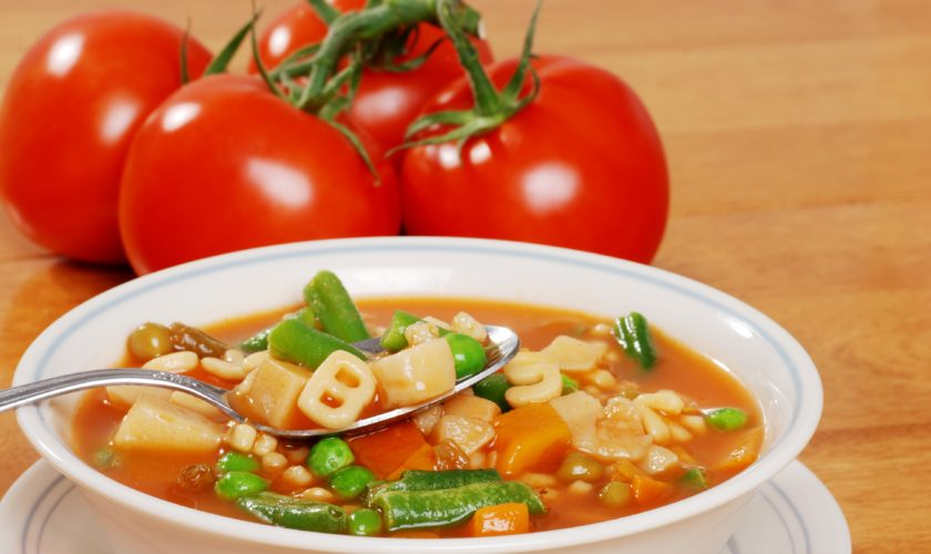 vegetable soup with tomato in the background